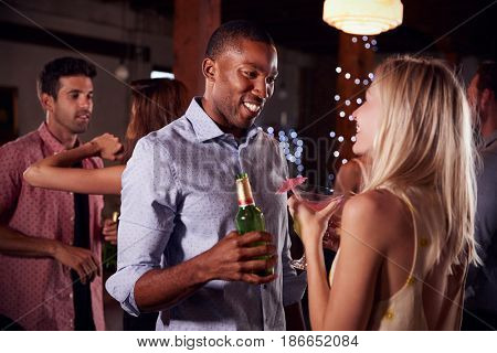 Black man and white woman talking at a party, side view