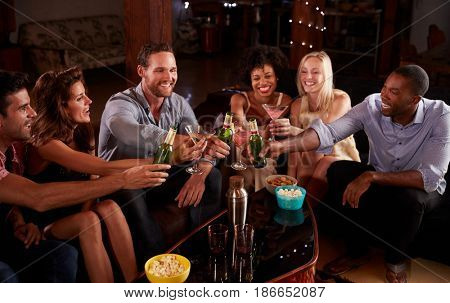 Young adult friends sit making a toast at a house party