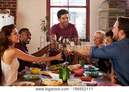 Host and friends making a toast at a dinner party