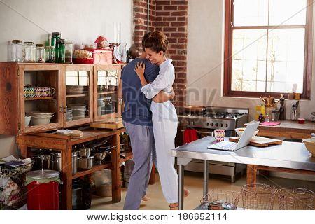 Hispanic couple in pyjamas embracing in kitchen