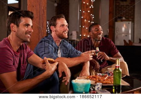 Three male friends hang out watching TV and eating pizza