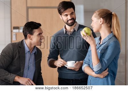 Keep fit. Positive woman putting right hand on the waist standing in semi position while looking at her coworkers