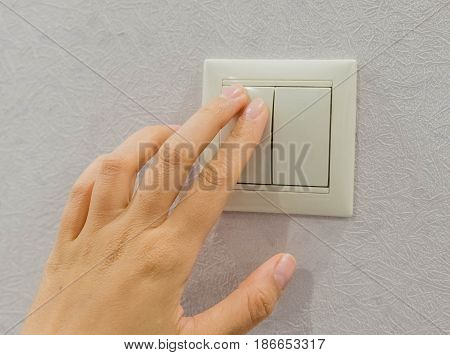save energy - switch off. Close up finger is turning on or off on light switch. Copy space.