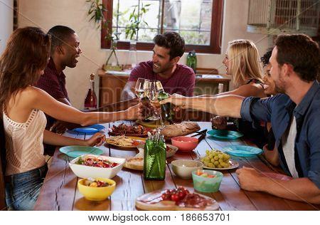 Six young adult friends making a toast at a dinner party