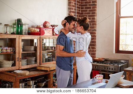 Happy Hispanic couple embracing in kitchen in the morning