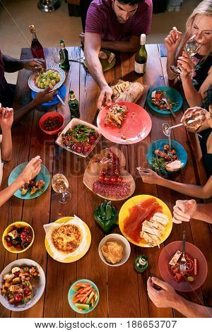 Overhead shot of friends passing food across a dinner table