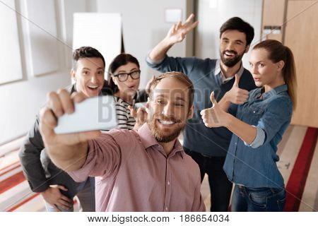 Making faces. Company of promising workers standing behind their colleague raising hands while looking straight at camera