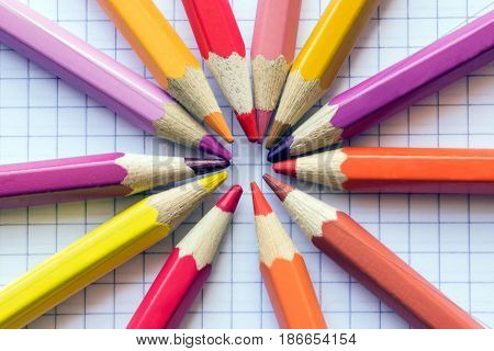 Colored pencils for drawing on the sheet of paper in a cage. Concept school friendship negotiation agreement creativity drawing.