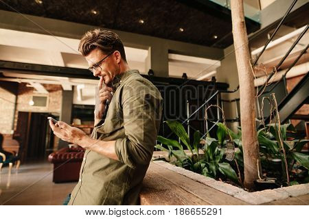 Side view of young man reading text message on his phone and thinking. Young businessman using mobile phone in office lobby.