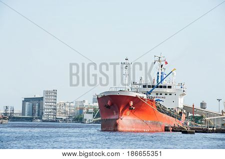 Logistic concept red Ship parked in the river. Waiting to dock and load the goods.