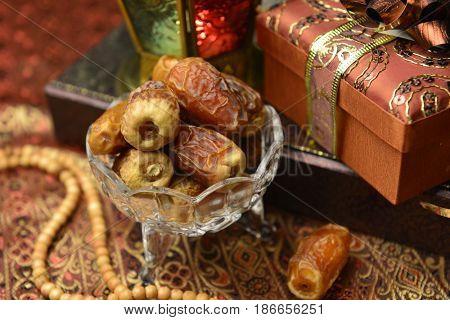 Elegantly wrapped Eid gift boxes, arranged along with sweet dates and Islamic rosary. Eid festive background.