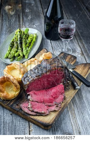 Barbecue dry aged Rib of Beef with green Asparagus and Yorkshire Pudding as close-up on an old cutting board