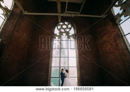 Happy stylish bride and groom holding each other in the belltower of old gothic cathedral.