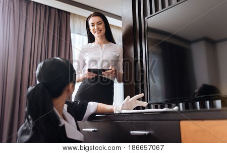 Hotel manager. Attractive cheerful young woman looking at the hotel maid and smiling while being happy with her work