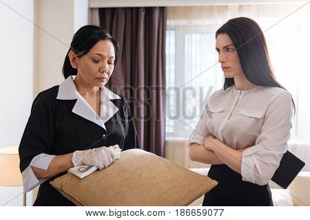 I couldnt clean it. Nice sad unhappy hotel maid standing near her manager and holding a cushion while working in the hotel