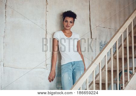 Beautiful african girl in white t-shirt standing at home.