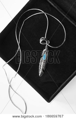 Silver feather shaped pendant with turquoise in jewel box closeup