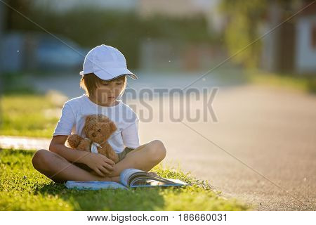 Beautiful Kid Boy, Reading A Book On The Street, Sitting Down With Teddy Bear