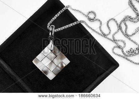 Nacre pendant on silver chain in black jewel box closeup