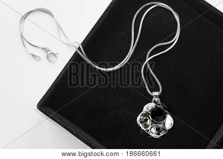 Crystal ball pendant on silver chain in black jewel box closeup