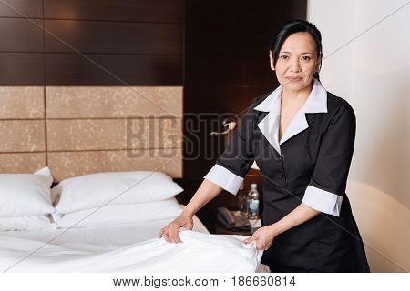 Professional maid. Positive delighted nice woman standing in the hotel room and holding a sheet while making the bed
