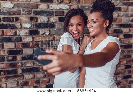 Two attractive African girls make selfie at home.