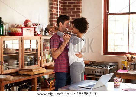 Young couple embracing in kitchen, three quarter length