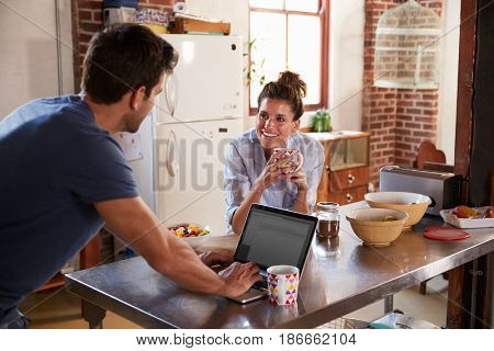 Happy Hispanic couple using computer in kitchen, waist up