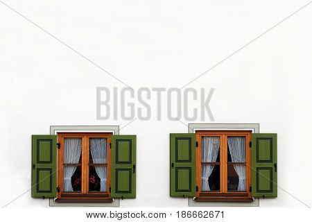 Two windows with green shutters open. Empty space above.