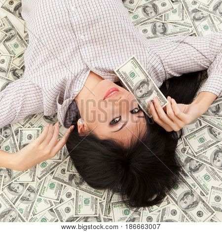 Young business woman resting upon money. People, money, banking, finances and savings concept.