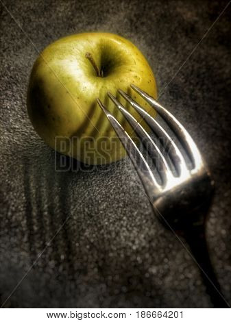Green apple and fork. Abstract concept photo. Low key. Film grain and artifacts for the dramatic effect.