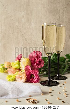 A bouquet of white and rose lisianthus, wedding ring, two glasses of champagne and а scattering of beads.