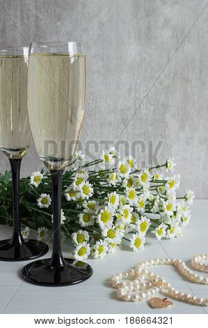 A bouquet of white chrysanthemum, two glasses of champagne and pearl necklace.