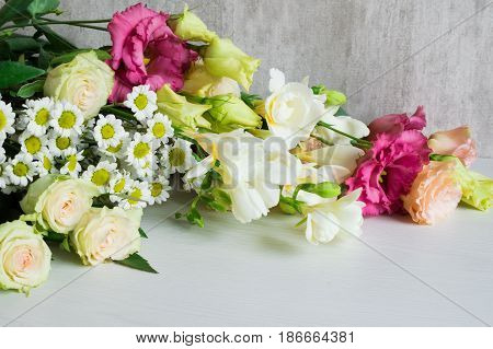 A bouquet of white freesia, lisianthus, chrysanthemum and roses on a white wooden background.