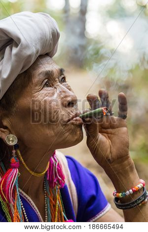 MAE KLANG LUANG, THAILAND - FEBRUARY 18, 2017 : A Karen hilltribe woman is smoking a large leaf cigarette in the Mae Klang Luang village near Chiang Mai, Thailand