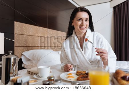 Beginning of the day. Beautiful nice happy woman sitting at the table and smiling while eating her breakfast