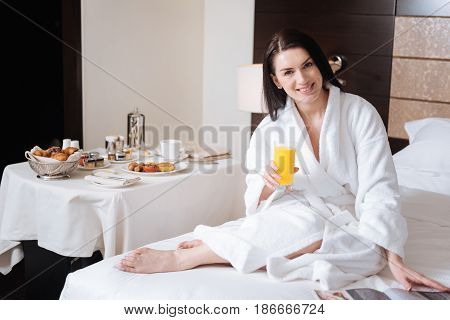 Full of energy. Positive joyful attractive woman sitting on the bed and holding a glass of juice while having breakfast