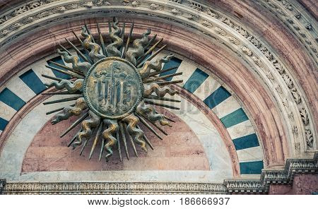 Religious symbol above a church door in Siena Italy