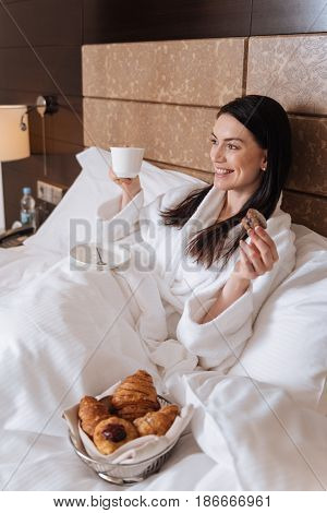 Start of the day. Happy delighted nice woman lying in her bed and eating breakfast while having a wonderful morning