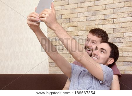 Happy gay couple resting on sofa and taking selfie with tablet at home
