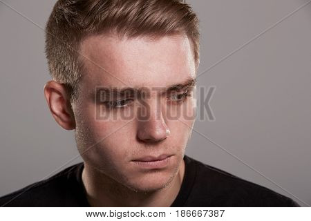 Sad young white man looking away, head and shoulders