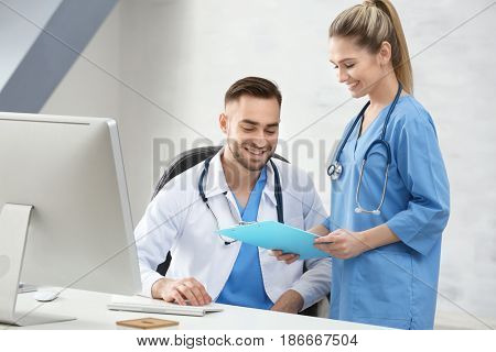 Doctor and medical assistant discussing issue in office