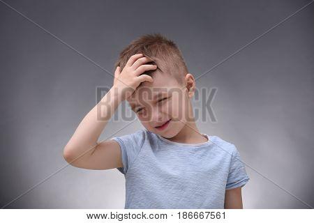Little boy suffering from headache on grey background