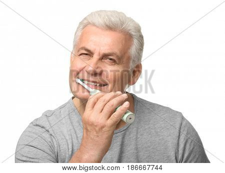 Senior man cleaning teeth on white background
