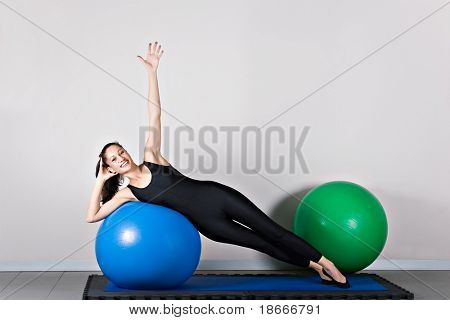 Side bend  with ball position. Pilates gymnastics is a Germanic evolution of yoga, used by athletes to improve flexibility and body fitness and by chiropractors for patient recovery.