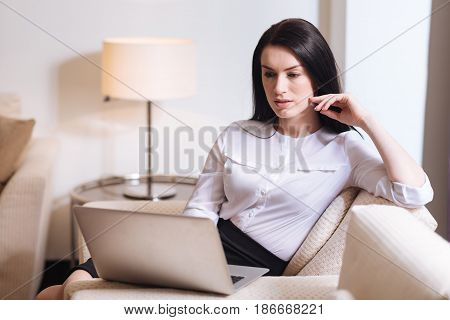 Modern technology. Serious nice pleasant woman sitting in the armchair and looking at the laptop screen while using it