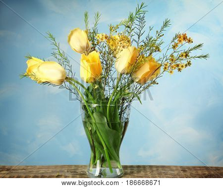 Vase with beautiful flowers on wooden table against color background