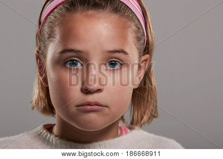 Sad nine year old girl looking to camera, close up head shot