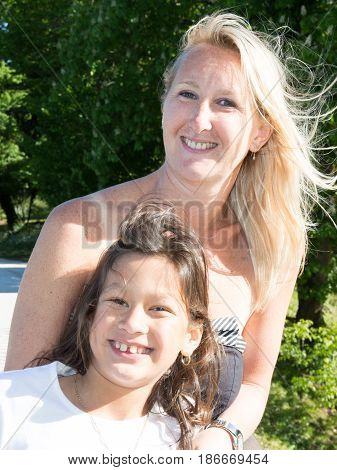 The Young Blonde Mother With Her Little Brown Girl