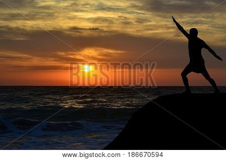 Man black silhouette in a yoga pose on the shore at sunrise